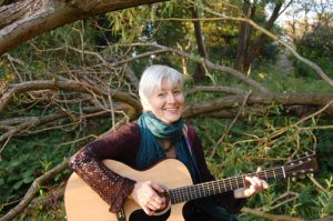 Zoe Mulford, with guitar, in a wooded English setting